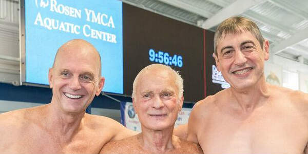 Rowdy Gaines, two-time Gold Medal Olympian and VP of Aquatics for the YMCA of Central Florida, Orlando hotelier Harris Rosen, and Dr. Lucky Meisenheimer, an early YMCA Aquatic Center supporter/contributor participate in an inaugural swim at the newly renamed Rosen YMCA Aquactic Center.
